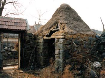 """(98年12月)这是院墙内一角放马草的""""小棚子"""",俗称""""将军帽""""。由于现代化的耕作,目前这种小屋已无人保留,这是仅存的一间""""将军帽"""""""