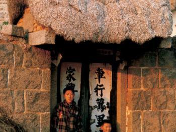"""(99年12月)""""海草房""""的门楼也盖着层层厚厚的海草,这是它独到之处"""