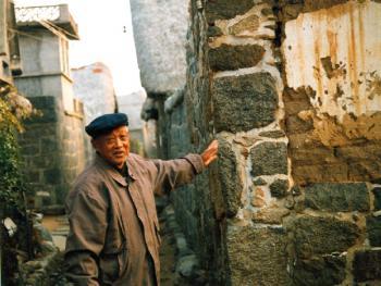 (99年12月)深居海草房群落的老人讲述着它的历史和房屋构造