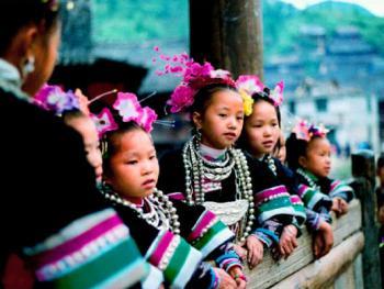 10.鼓楼堂里对歌的侗家小孩。侗族大歌早已蜚声海内外,这种多声部组合而成的民间合唱的教学点就是位于寨子中心的鼓楼堂里。,人们经常在这集合,特别是那些小孩歌队,少则十几、多则二三十人,他们一边玩,一边练歌,成为千里侗寨的一大亮点。1996年11月,从江县