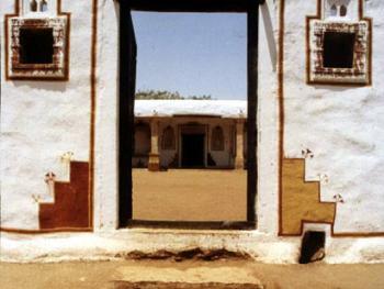 主门和房子里的样子。进入主门的时候,可以看见里面有片宽阔的空地。里面是有顶的门廊和石柱。空地是泥土铺设的。雨水流过的时候,就可以排出屋外