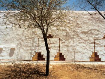 20英尺高的外墙上画着白色的柱子和很多门。都是选用沙土,泥浆和植物等自然颜色