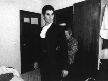 5.在一间小旅馆的房间里做准备。伊艾•维纳瑞照着镜子,他的助手将他打扮成战斗的装束。
