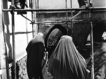 脚手架。两个妇女经过由两个男人正在修建的喀布尔女子办公楼。