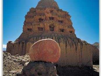 在刻有佛像的玛尼石后,古格遗址的佛塔蔚然屹立。
