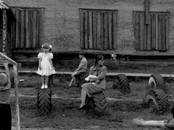 在破旧的学校附近,年轻的母亲和女儿。Baikit村